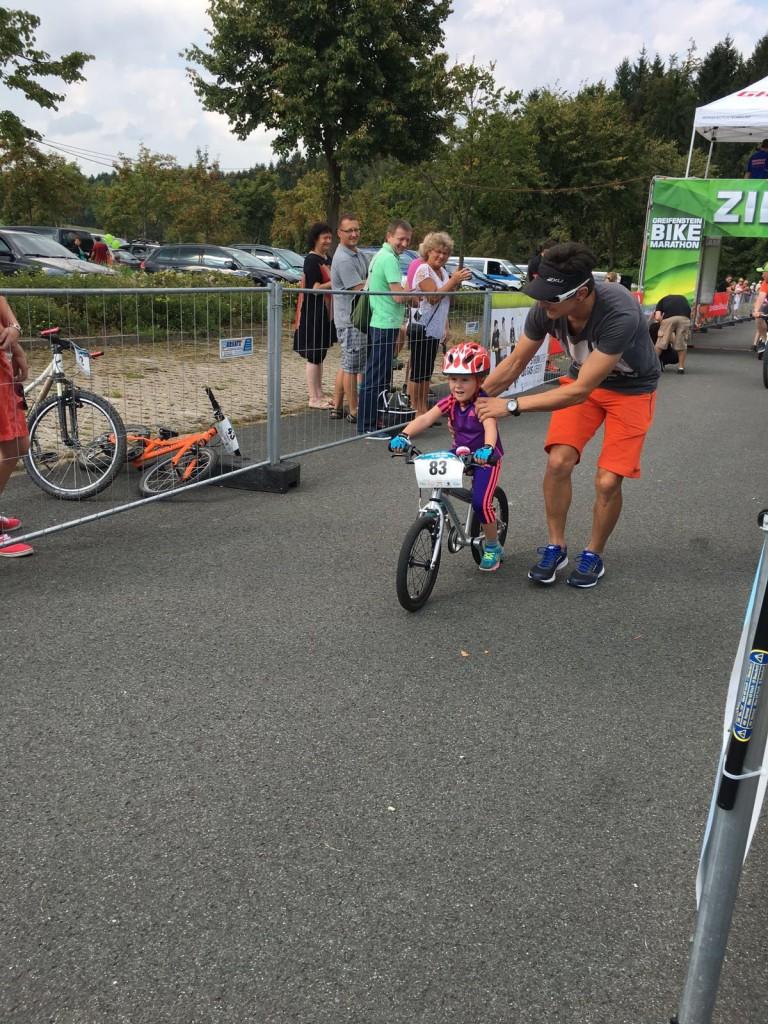 Suvi Milena Schubert überquert als Erste in ihrer Altersklasse die Ziellinie und wird von Papa Michael empfangen.