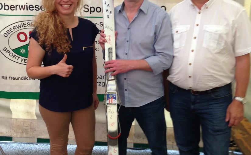 Karolin Tottewitz (links) und Michael Meyer (rechts) überreichen einen silbernen Ski an Falk Weißbach, Vorsitzender des Oberwiesenthaler Sportvereins, zum Jubiläum